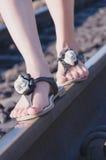 Gambe femminili in scarpe da tennis sulla ferrovia della ferrovia fotografia stock libera da diritti