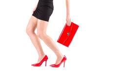 Gambe femminili in scarpe ed in borsa rosse a disposizione Fotografia Stock Libera da Diritti