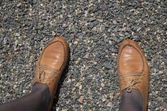 Gambe femminili in scarpe marroni su un fondo di ghiaia Immagine Stock