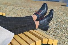 Gambe femminili in scarpe nere in una sedia di salotto sulla sponda del fiume fotografia stock