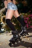 Gambe femminili sexy nei pattini di rullo Fotografie Stock