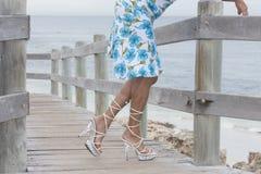 Gambe graziose in tacchi alti rilassati alla spiaggia Fotografia Stock Libera da Diritti