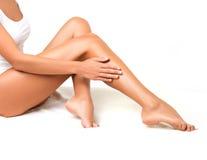 Gambe lunghe della donna isolate su bianco. Fotografia Stock