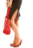Gambe lunghe e borsa rossa sopra bianco Fotografia Stock