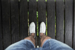 Gambe maschii in breve e scarpe bianche su un ponte di legno, vista superiore Immagine Stock Libera da Diritti