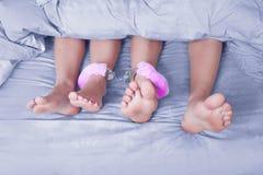 Gambe maschii e femminili ammanettate, giocattolo del sesso blu immagini stock libere da diritti