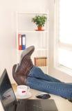 Gambe maschii sulla scrivania Fotografie Stock Libere da Diritti