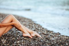 Gambe sexy del ` s delle donne belle sulla spiaggia fotografia stock