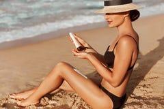 Gambe sexy della donna del bikini di abbronzatura che si rilassano riposarsi sulla spiaggia Cura del corpo di protezione di invec fotografia stock