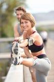 Gambe strecthing delle coppie di Athleltic dopo avere corso Immagini Stock Libere da Diritti