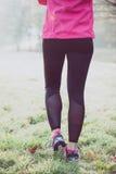 Gambe sulla pista di inverno, stile di vita sano della donna del corridore Fotografia Stock