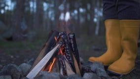 Gambe umane in stivali di gomma gialli che stanno vicino ad un fuoco bruciante nella foresta archivi video