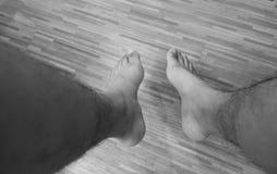 Gambe umane sul pavimento di legno Fotografia Stock
