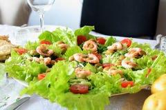Gamberetti con le foglie ed i pomodori ciliegia dell'insalata su una tavola di cena immagini stock