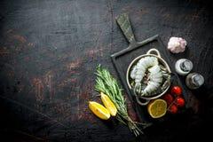Gamberetti crudi non cucinati con i pomodori, le fette del limone ed i rosmarini immagine stock libera da diritti