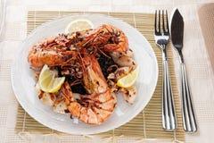 Gamberetti enormi e calamari cotti con riso nero Fotografie Stock