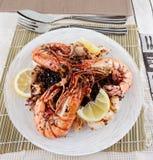 Gamberetti enormi e calamari cotti con riso nero Fotografia Stock