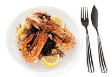 Gamberetti enormi e calamari cotti con riso nero isolato su briciolo Immagini Stock