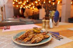 Gamberetti fritti con il limone arrostito sulla tavola del ristorante immagini stock