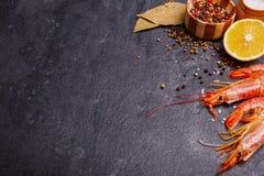 Gamberetti reali, limone, una miscela dei peperoni, un sale e parecchie foglie di alloro sulla tavola Immagine Stock