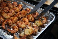 Gamberi del barbecue sulla griglia con le pinze di presa Immagini Stock