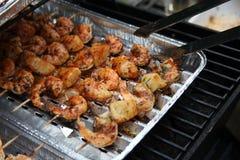 Gamberi del barbecue sulla griglia con le pinze di presa Immagine Stock