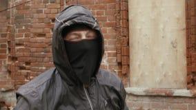 Gamberro agresivo en la máscara que amenaza a la cámara con el bate de béisbol almacen de metraje de vídeo