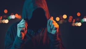 Gamberro anónimo con sudadera con capucha en el cerco urbano fotos de archivo libres de regalías