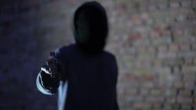 Gamberro anónimo que amenaza con el arma, agresión del robo, criminal armado almacen de metraje de vídeo