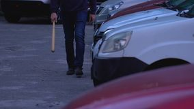 Gamberro arrogante con el bate de béisbol que va a destruir y a robar los coches en estacionamiento almacen de video