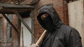 Gamberro de la calle en máscara negra con el bate de béisbol en la calle criminal que mira a la cámara almacen de metraje de vídeo