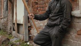 Gamberro en la ropa negra que sostiene el bate de béisbol y que espera cerca del edificio al aire libre almacen de video