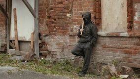 Gamberro en máscara negra y capilla con el bate de béisbol que se inclina detrás en la pared de ladrillo metrajes