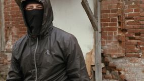 Gamberro enojado en máscara negra y capilla que hace retroceso a la cámara metrajes