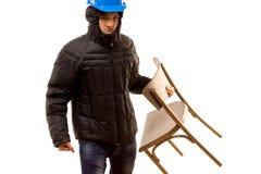 Gamberro joven enojado que lleva una silla de madera Fotografía de archivo