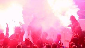 Gamberros que usan las llamaradas ardiendo, bombas de humo en las tribunas durante el partido de fútbol almacen de metraje de vídeo