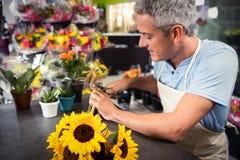 Gambi maschii della guarnizione del fiorista dei fiori al negozio di fiore fotografie stock libere da diritti