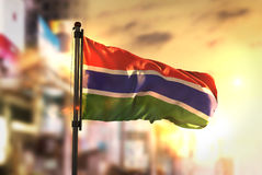 The Gambia Flag Against City Blurred Background At Sunrise Backl. Ight Sky Royalty Free Stock Image