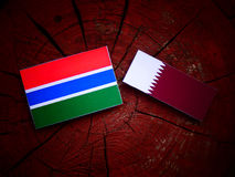 Gambian flag with Qatari flag on a tree stump isolated. Gambian flag with Qatari flag on a tree stump Royalty Free Stock Image