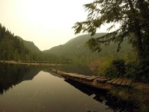 Gambier lake, Vancouver VC Canada. A view across Gambier Lake on Gambier island. The slight misted sky from a distant forrest fire and perfectly still waters Royalty Free Stock Image