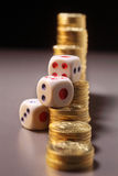 Gamble. Dices rest on top of the coins stock photography