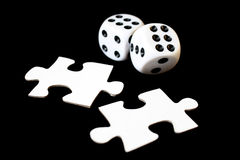 Gamble. Two dices and puzzle pieces on a black background royalty free stock images