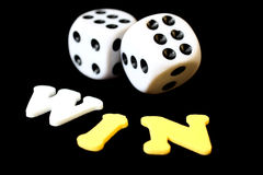 Gamble. Two dices and the letters spelling 'win' on a black background royalty free stock images