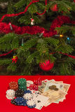 Gamble by Christmas. Casino chips, cards dices and money on red table with a Christmas tree on background Royalty Free Stock Image