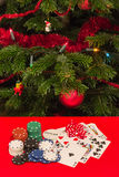 Gamble by Christmas. Casino chips, cards dices and money on red table with a Christmas tree on background Royalty Free Stock Photo