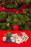 Gamble by Christmas. Casino chips, cards and dices on red table with a Christmas tree on background Royalty Free Stock Image