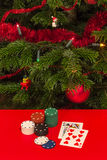 Gamble by Christmas. Casino chips and cards on red table with a Christmas tree on background Stock Image