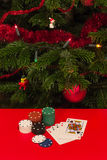 Gamble by Christmas. Casino chips and cards on red table with a Christmas tree on background Stock Images