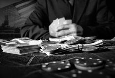 Gamble. A poker table of money, cards and poker chips.  With US flag and factory in background.  Life's a gamble and is getting more difficult Royalty Free Stock Images