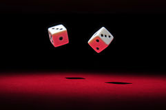 Gamble: throwing the dices. Two dices falling on a red surface. The light in the scene is spot like Royalty Free Stock Images